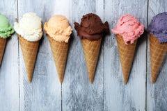 Scoops de crème glacée de différentes couleurs et saveurs avec la décoration de baies, d'écrous et de fruits sur le fond blanc images stock