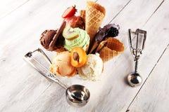 Scoops de crème glacée de différentes couleurs et saveurs avec la décoration de baies, d'écrous et de fruits sur le fond blanc photographie stock libre de droits