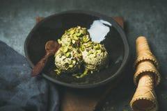 Scoops faits maison de crème glacée de pistache avec les écrous brisés dans le plat Photographie stock