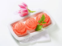 Scoops of fruit sherbet and fresh tulips. Scoops of pink ice cream and fresh tulips Stock Photography