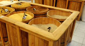 Scoops in groats at wooden barrels closeup Stock Photo