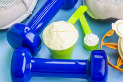 Scoops with pure whey protein and creatine with sport items around Stock Photography