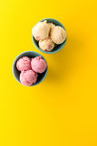 Scoops savoureux de fraise de vanille de crème glacée dans des cuvettes bleues sur le yello Photographie stock libre de droits