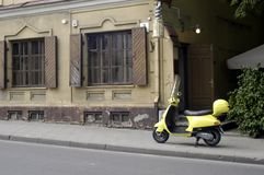 Scooter. Yellow motor scooter left in front of the cafe entrance Royalty Free Stock Photography