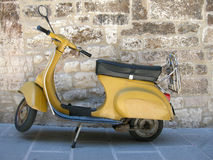 Scooter. A yellow Italian scooter parked at a stone wall in Italy Stock Images