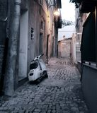 Scooter in alleyway. White motor scooter parked in narrow Sicilian alleyway at dusk, Italy Stock Images