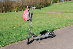 Scooter and backpack next to the green meadow. Stock Image
