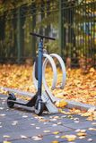 Scooter, bike stopping in parking, sidewalk with yellow falling leaves. Autumn mood concept. Scooter, bike stopping in parking, sidewalk with yellow falling royalty free stock images