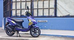 Scooter bleu sur la bordure de trottoir photographie stock libre de droits