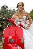 Scooter Bride. A bride sitting on a red scooter Royalty Free Stock Image