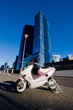 Scooter and city scape. Pink modern scooter on the city street Royalty Free Stock Image