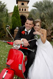 Scooter Couple. A wedding couple sitting on a red scooter Royalty Free Stock Images