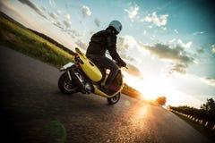 Scooter d'équitation d'homme pendant le coucher du soleil Photographie stock libre de droits