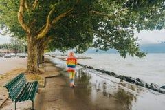 Scooter d'équitation de fille d'enfant par le lac un jour pluvieux photos libres de droits