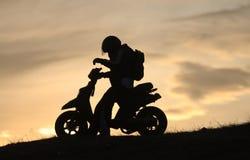 Scooter dans le coucher du soleil Photographie stock libre de droits
