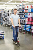 Scooter de essai d'homme dans la boutique de sports Photo stock