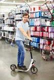 Scooter de essai d'homme dans la boutique de sports Photo libre de droits