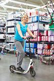 Scooter de essai de femme dans la boutique de sports Photo stock