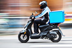 Scooter delivery service in motion blur. Picture of a scooter delivery service in motion blur royalty free stock image