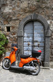 Scooter and door in medieval city in Italy. Scooter and door in contrasting colors in medieval city Civita di Bagnoregio in Italy Stock Photos