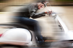 Scooter driver in a crazy ride Royalty Free Stock Image