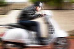 Scooter driver in a crazy ride Stock Images