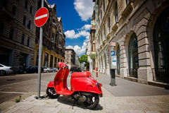 Scooter et poteau de signalisation rouges Photographie stock libre de droits