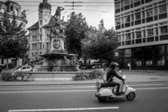 Scooter in front of a fountain in St. Gallen, Switzerland stock images