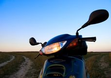 Scooter with the included headlight. Modern scooter with the included headlight on the summer evening field Stock Photos