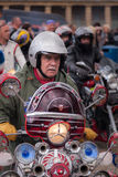 Scooter Man. A mature man riding a heavily customised scooter with lots of lights and mirrors. He is wearing a silver grey open faced helmet and a green parka Royalty Free Stock Photo