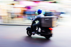 Scooter messenger on the road in motion blur. Picture of a scooter messenger on the road in motion blur Stock Photography