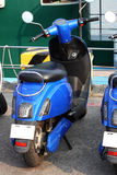 Scooter / Moped parked by harbour. A blue scooter parked by harbour in a relatively dry sunny day Royalty Free Stock Photo