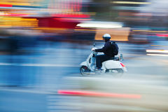 Scooter in motion. Blur with light trails of city traffic in the evening Royalty Free Stock Images