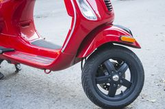 Red scooter. A motorbike scooter parked on a city street representing environmentally friendly transportation choices and reduced carbon footprint Royalty Free Stock Photo