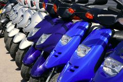 Scooter motorbikes in a row with perspective. Line Royalty Free Stock Images