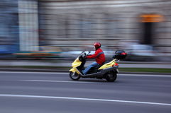 Scooter move. Red coat man ride a scooter in Budapest at main street stock images