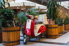 Scooter near the restaurant with pizza. Surrounded by palm trees royalty free stock image