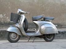Scooter old. Silver scooter parked on pavement royalty free stock photos