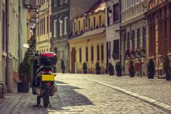 Scooter parked on alley. Classic scooter parked on an empty paved alley in the historic center of Brasov city, Romania Stock Photography