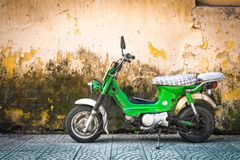 Scooter parked at old building in Vietnam, Asia. Green scooter against old house. Weathered wall as background. Urban street in Vietnam, Asia. Moped parked at royalty free stock photography