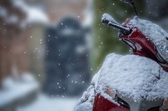 A scooter parked outside a house during snowfall with a shallow depth of field. Snow flakes against a contrasty background are one hell of a sight. I did manage Royalty Free Stock Photo