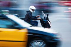 Scooter rider overtake a taxi Royalty Free Stock Images