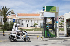 Scooter rider and pillion passenger at gas station Stock Images
