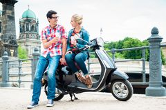 Scooter riding tourists drinking coffee in Berlin. Tourists, women and man, on scooter trip in Berlin taking a rest on the Museum Island Royalty Free Stock Photo