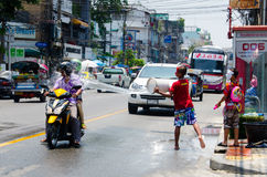 Scooter Splash. Bangkok, Thailand, 14 April 2015. Children by the roadside splashing passing motorists with buckets of water. The annual Songkran water festival Royalty Free Stock Images