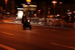 The Scooter. Two people on a scooter by night Royalty Free Stock Photos