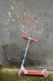 Scooter utilisé de coup-de-pied d'enfant près de mur images libres de droits