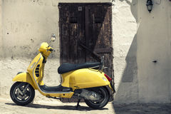 Scooter yellow motorcycle in front of old houses with white wall. A scooter is parked in front of an old house with wooden door consumed. Typical scene Italian Royalty Free Stock Photo