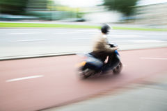 Scooterist in motion Royalty Free Stock Photo