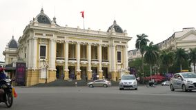 Scooters, cars, traffic and people outside Hanoi Opera House, Hanoi, Vietnam stock footage
